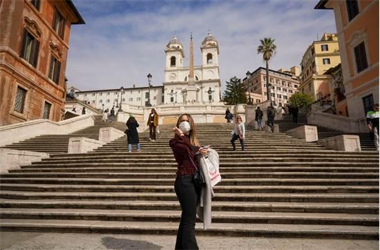אשה עם מסכה מצטלמת ליד המדרגות הספרדיות ברומא. מדובר באתר תיירות פופלארי מאוד בקרב תיירים / צילום: Andrew Medichini, AP