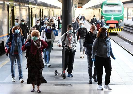 נוסעים עוטים מסכות בתחנת הרכבת במילאנו לאחר הקלות בסגר שהוטל על איטליה / צילום: FLAVIO LO SCALZO, רויטרס
