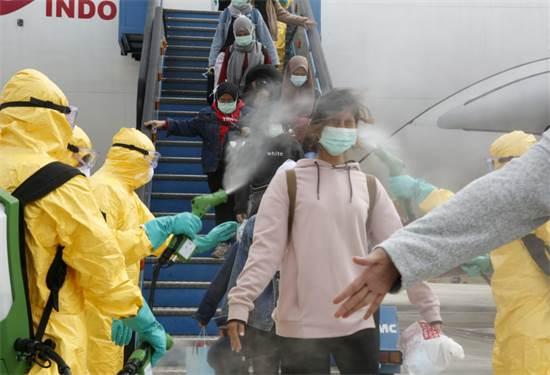 צוותים בשדה התעופה באינדונזיה בודקים נוסעים שחזרו מווהאן / צילום: רויטרס