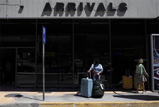 תיירית מגרמניה בשדה התעופה ברודוס, יוון, אחרי פתיחת הגבולות לתיירות / צילום: Alkis Konstantinidis, רויטרס