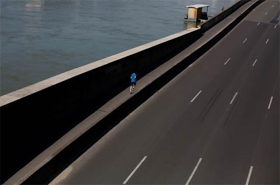 גבר רץ לאורך נהר הסן והכביש המהיר והריק בפריז, צרפת / צילום: Thibault Camus, AP