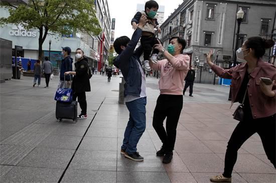 ילד והוריו ברחובות ווהאן ביום השחרור לאחר הסגר / צילום: AP