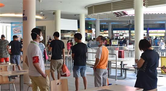 מפקח ריחוק חברתי (עם הסרט האדום על הזרוע) שומר שהעומדים בתור לטייק אוויי לא מתקרבים זה לזה, סינגפור  / צילום: YK Chan, AP