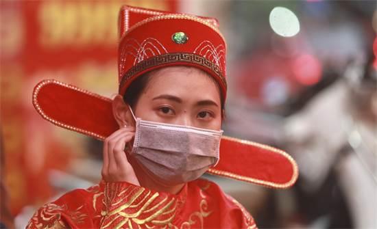 אישה בתחפושת אלת השגשוג ומסכת פנים / צילום: Hau Dinh, AP