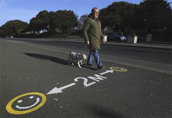 סימון דרכים שמזכיר לשמור על מרחק של 2 מטר לפחות בדבלין, אירלנד / צילום: Brian Lawless/PA, AP