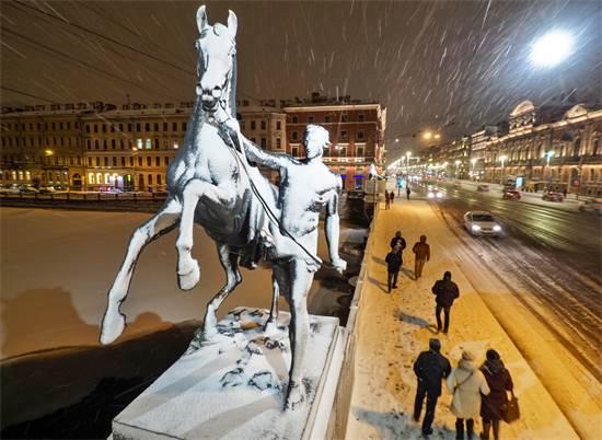 אנשים חולפים ליד אחד מארבעת פסלי הסוסים המפורסמים של גשר  / צילום: Dmitri Lovetsky, AP