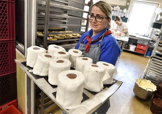מוכרת במאפייה בעיר דורטמונד מחזיקה במגש עם עוגות בצורת נייר טואלט / צילום: Martin Meissner, AP