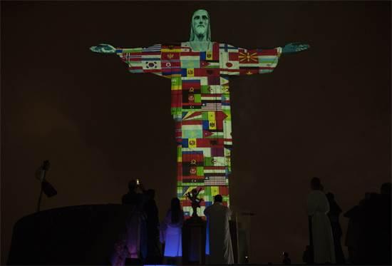 פסל ישו בריו דה ז'נרו בברזיל מואר בדגלי המדינות הנגועות בנגיף הקורונה  / צילום: Silvia Izquierdo, AP
