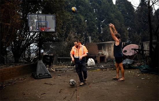 שני גברים ליד ביתם שנשרף בשריפות באוסטרליה / צילום: Tracey Nearmy, רויטרס