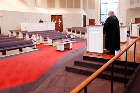 """כומר בארה""""ב מעביר דרשה בכנסייה ריקה. הדרשה והתפילה שודרו באינטרנט למאמינים / צילום: Mark Humphrey, AP"""