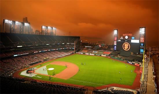 משחק בייסבול בפארק אורקל בסן פרנסיסקו ברקע לשמים שכתומים מעשן השרפות / צילום: Tony Avelar, AP