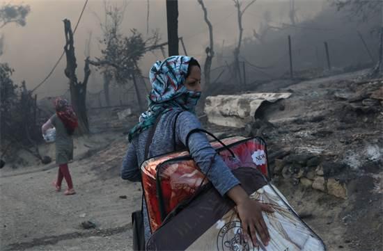 פליטה עוזבת את מחנה הפליטים מוריה לאחר שפרצה בו אש / צילום: Elias Marcou, רויטרס