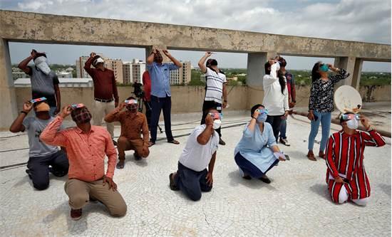 תושבים בעיר גנדינגאר בהודו צופים בליקוי חמה חלקי / צילום: Amit Dave, רויטרס