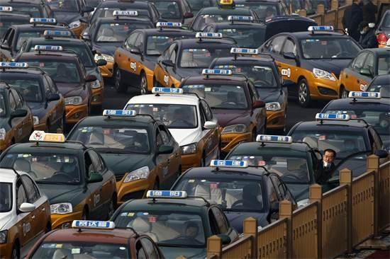 מוניות שמחכות לנוסעים ליד תחנת הרכבת בבייג'ינג' / צילום: Andy Wong, AP