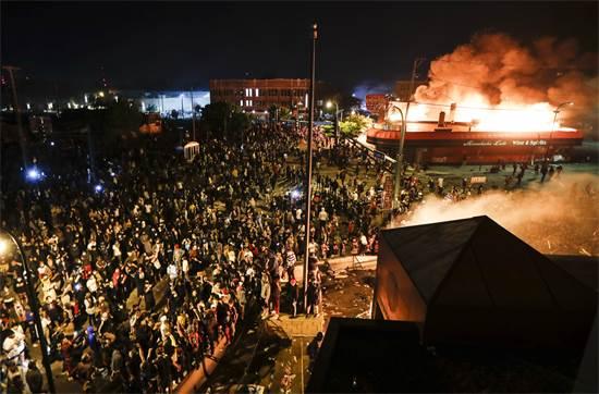 מפגינים מול מבנה המשטרה הבוער של מחוז 3 במינאפוליס ביום שישי / צילום: John Minchillo, AP