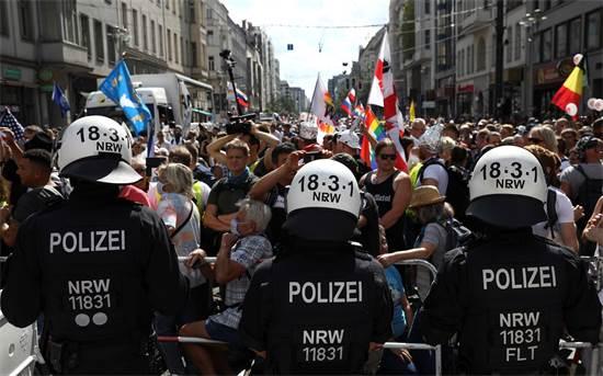 שוטרים עומדים מול הפגנה נגד מגבלות הקורונה בברלין / צילום: Christian Mang, רויטרס