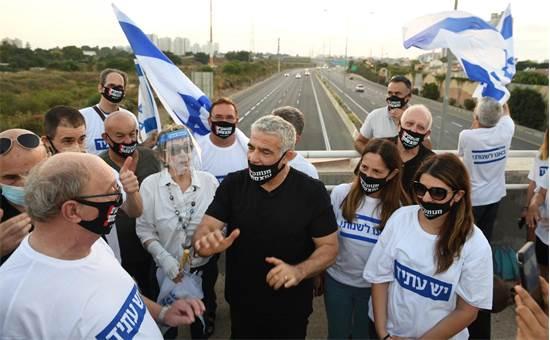 """יאיר לפיד ופעילי יש עתיד במחאת הגשרים בגשר / צילום: אלעד גוטמן, יח""""צ"""