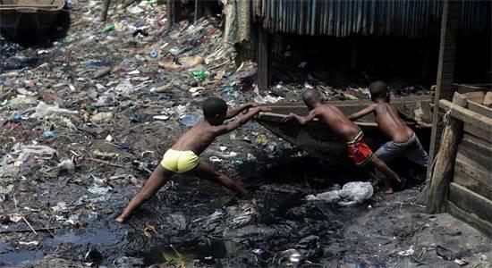 ילדים גוררים ספינת קנו בשכונות העוני המוצפות בניגריה / צילום: סאנדיי אלבאמה, AP