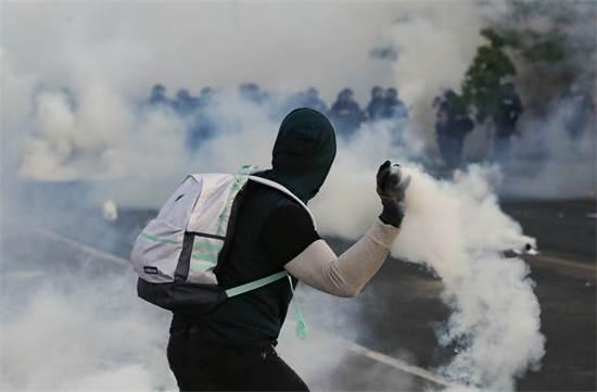 מפגין זורק בחזרה רימון גז אל עבר השוטרים בסנט פול, מינסוטה  / צילום: John Minchillo, AP