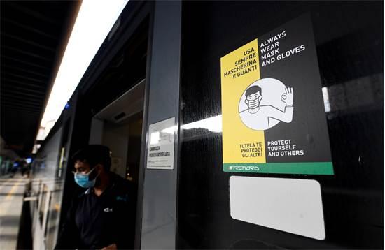 שלט בתחנת הרכבת התחתית במילנו שקורא לנוסעים לעטות מסכות וללבוש כפפות / צילום: FLAVIO LO SCALZO, רויטרס
