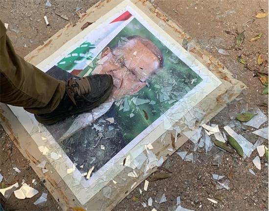 מפגין דורך על תמונת נשיא לבנון מישל עאון במשרד החוץ בביירות / צילום: Ellen Francis, רויטרס