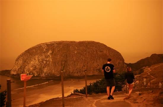 אנשים צועדים לצד החוף של האוקיאנוס השקט, באורגון. עשן השריפות שינה את צבע השמים / צילום: Carlos Barria, רויטרס