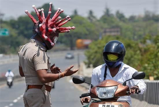 שוטר עם קסדה בצורת נגיף הקורונה מבקש מאדם בהודו לא לצאת מביתו / צילום: P. Ravikumar, רויטרס