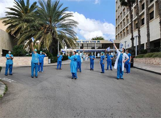 """המטס חולף מעל בי""""ח מאיר בעוד הצוות הרפואי מנופף בדגלי ישראל ומוחא כפיים / צילום: דוברות משרד הבריאות, יח""""צ"""