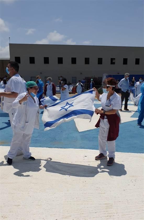 """בגליל מניפים דגלי ישראל בעת שהמטס חולף מעל / צילום: דוברות משרד הבריאות, יח""""צ"""
