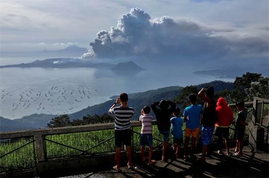 תושבים מסתכלים על התפרצות הר הגעש טאאל / צילום: Eloisa Lopez, רויטרס