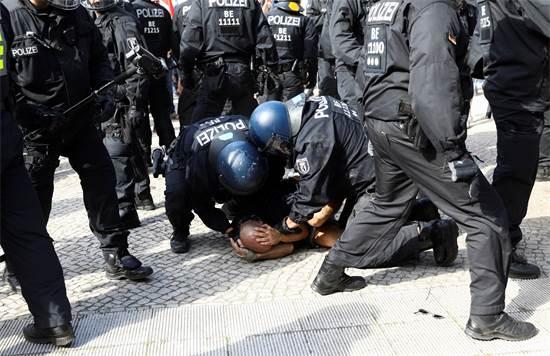 שוטרים עוצרים מפגין בהפגנה נגד הגבלות הקורונה בברלין / צילום: Christian Mang, רויטרס