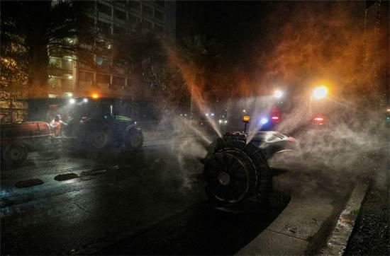 עובדים משתמשים במרססי חיטוי ענקיים בעיר סנטיאגו בצ'ילה / צילום: Esteban Felix, AP