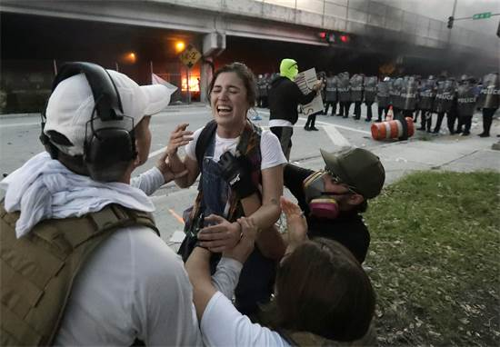 מפגינים עוזרים לסייע למפגינה שנפגעה מכדור גומי משטרתי בגרון במיאמי, פלורידה ביום שבת / צילום: Wilfredo Lee, AP