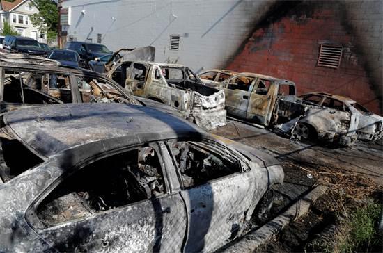 חניון במיניאפוליס בשבת בבוקר, לאחר שבליל שישי מפגינים העלו את הרכבים באש / צילום: Julio Cortez, AP