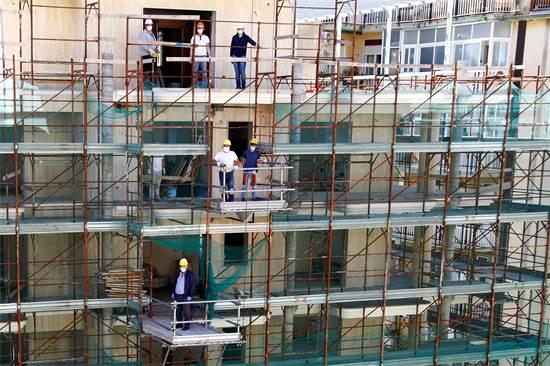 פועלים עוטים מסכה באתר בנייה בקטניה באיטליה שנפתח לאחר ההקלות בסגר  / צילום: Antonio Parrinello