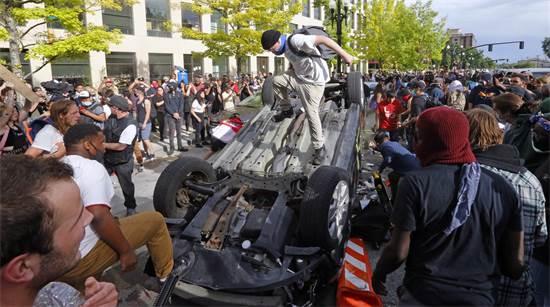 רכב שנהפך ונהרס באלימות על ידי המפגינים בסולט לייק סיטי ביוטה / צילום: Rick Bowmer, AP