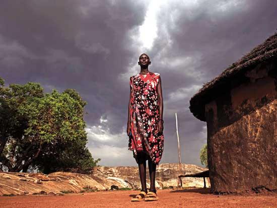 אישה בסמוך לביתה בסודן./ צילום: רויטרס Finbarr O'Reilly