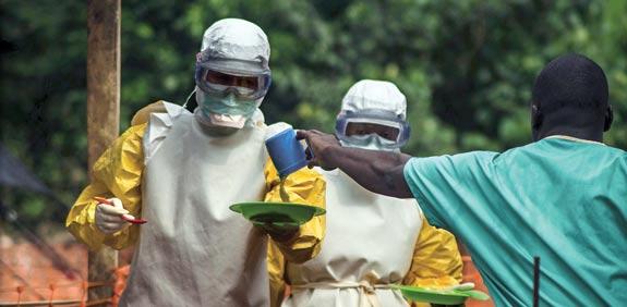 צוות רפואי מעביר אוכל לחולה אבולה בסיירה לאון / צילום: רויטרס