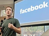 מארק צוקרברג על רקע שלט פייסבוק / צלם: רויטרס