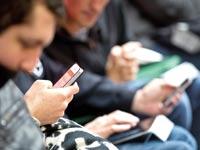 מכורים לסמארטפון / צילום: בלומברג