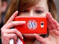 אוהדת באיירן מינכן משתמשת בטלפון הסלולרי שלה / צלם: רויטרס