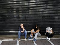 יוון, אנשים יושבים מחוץ לבנק סגור / צילום: רויטרס