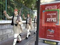 אנשי המשמר הנשיאותי ליד כרזת בחירות של סיריזה / צילום: רויטרס