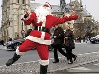 אדם מחופש לסנטה קלאוס וברקע כנסיית נוטרה דאם בפריז / צילום: רויטרס