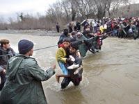 מבקשי מקלט חוצים נהר על גבול יוון–מקדוניה / צילום: רויטרס