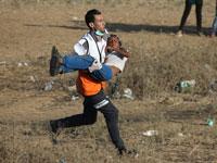ילד עזתי מפונה במהלך הפגנה בגדר / צילום: רויטרס- Ibraheem Abu Mustafa