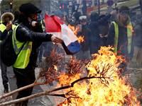 מפגין באפוד צהוב שורף את דגל צרפת בפריז / צילום: רויטרס - Stephane Mahe
