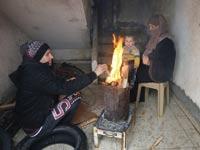 משפחה עזתית מתחממת / צילום: רויטרס, Ibraheem Abu Mustafa