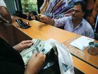 החלפת כספים בעמדת צ'יינג' פומבית./צילום: רויטרס  Morteza Nikoubazl