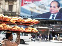 אדם נושא כיכרות לחם בקהיר על רקע שלט תעמולה בעד הנשיא סיסי /  צילום: רויטרס